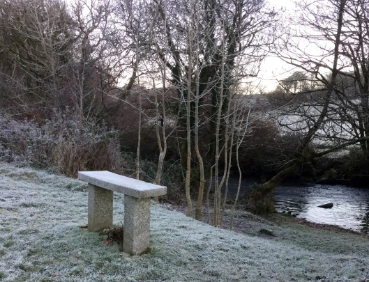 A granite bench overlooking a quite stretch of river