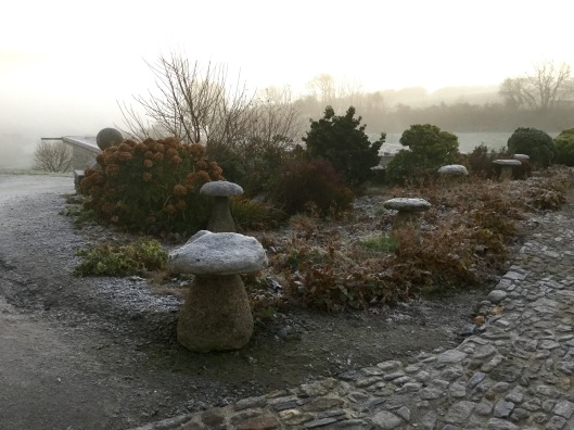 Staddle stones in a mixed border.